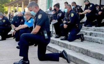George Floyd, non solo violenze: i poliziotti si inginocchia